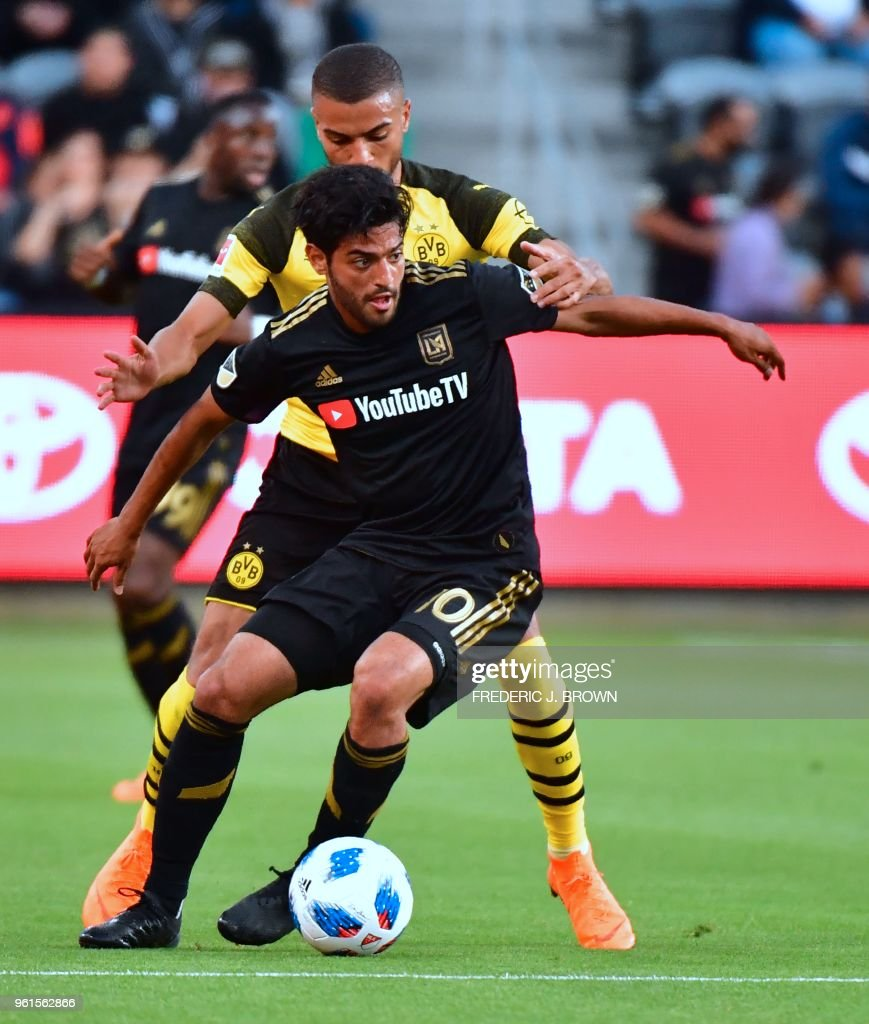 Carlos Vela (#10) of LAFC (Los Angeles Football Club) vies for the ball with Jeremy Toljan (rear) of Borussia Dortmund during their international soccer friendly in Los Angeles, California on May 22, 2018. - The game ended in a 1-1 draw.
