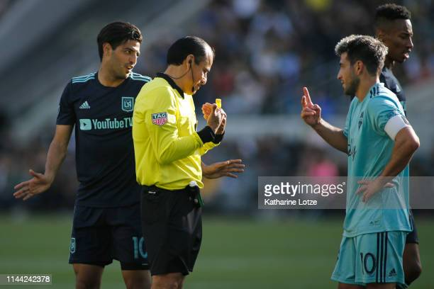 Carlos Vela of Los Angeles FC and Nicolas Lodeiro of Seattle Sounders argue with the official's call during the second half of a game at Banc of...