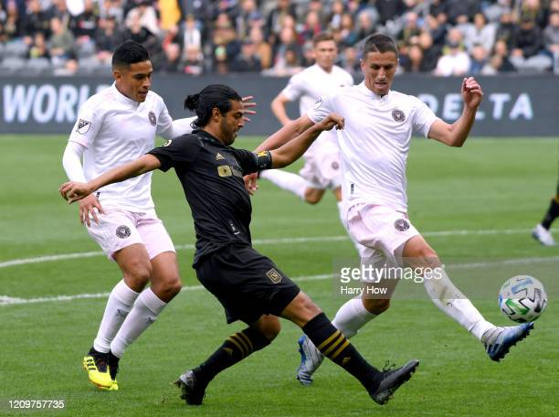 Carlos Vela of Los Angeles FC attempts a cross in front of Victor Ulloa and Ben Sweat of Inter Miami CF during the first half at Banc of California...