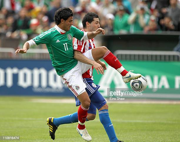 Carlos Vela of Mexico and Antolin Alcaraz of Paraguay go for the ball during their international friendly match at OaklandAlameda County Coliseum on...