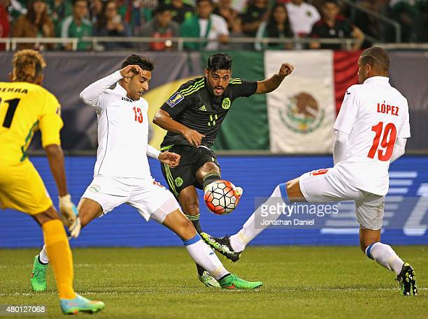 Carlos Vela of Mexico fires a shot between Jorge Corrales and Yasmani Lopez of Cuba during a match in the 2015 CONCACAF Gold Cup at Soldier Field on...