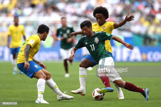 Carlos Vela of Mexico is challenged by Willian and Fagner of Brazil during the 2018 FIFA World Cup Russia Round of 16 match between Brazil and Mexico...