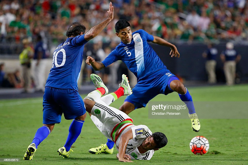 Carlos Vela #5 of Mexico is upended as he attempts to control the ball against Jose Contreras #10 and Moises Hernandez #5 of Guatemala during the second half of the 2015 CONCACAF Gold Cup group C match at University of Phoenix Stadium on July 12, 2015 in Glendale, Arizona. Guatemala and Mexico finished in a 0-0 tie.