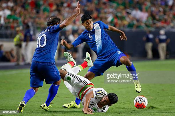 Carlos Vela of Mexico is upended as he attempts to control the ball against Jose Contreras and Moises Hernandez of Guatemala during the second half...