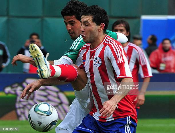 Carlos Vela of Mexico struggles for the ball with Antolin Alcaraz of Paraguay during an International Friendly Match at Oakland Alameda County...
