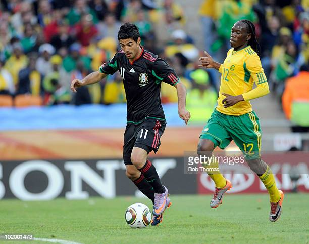 Carlos Vela of Mexico with Reneilwe Letsholonyane of South Africa during the 2010 FIFA World Cup South Africa Group A match between South Africa and...