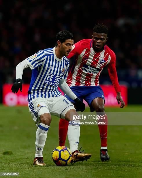 Carlos Vela of Real Sociedad de Futbol competes for the ball wi th Thomas Teye Partey of Atletico de Madridduring the La Liga match between Club...