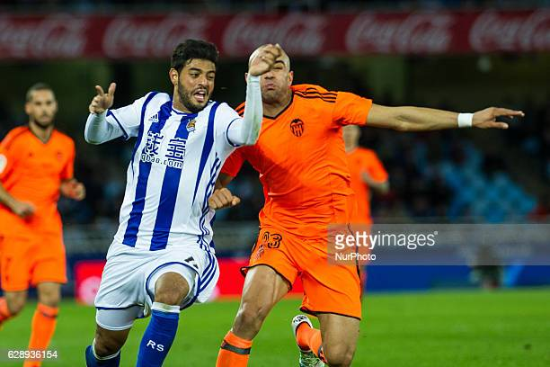 Carlos Vela of Real Sociedad duels for the ball with Aymen Abdennour of Valencia during the Spanish league football match between Real Sociedad and...