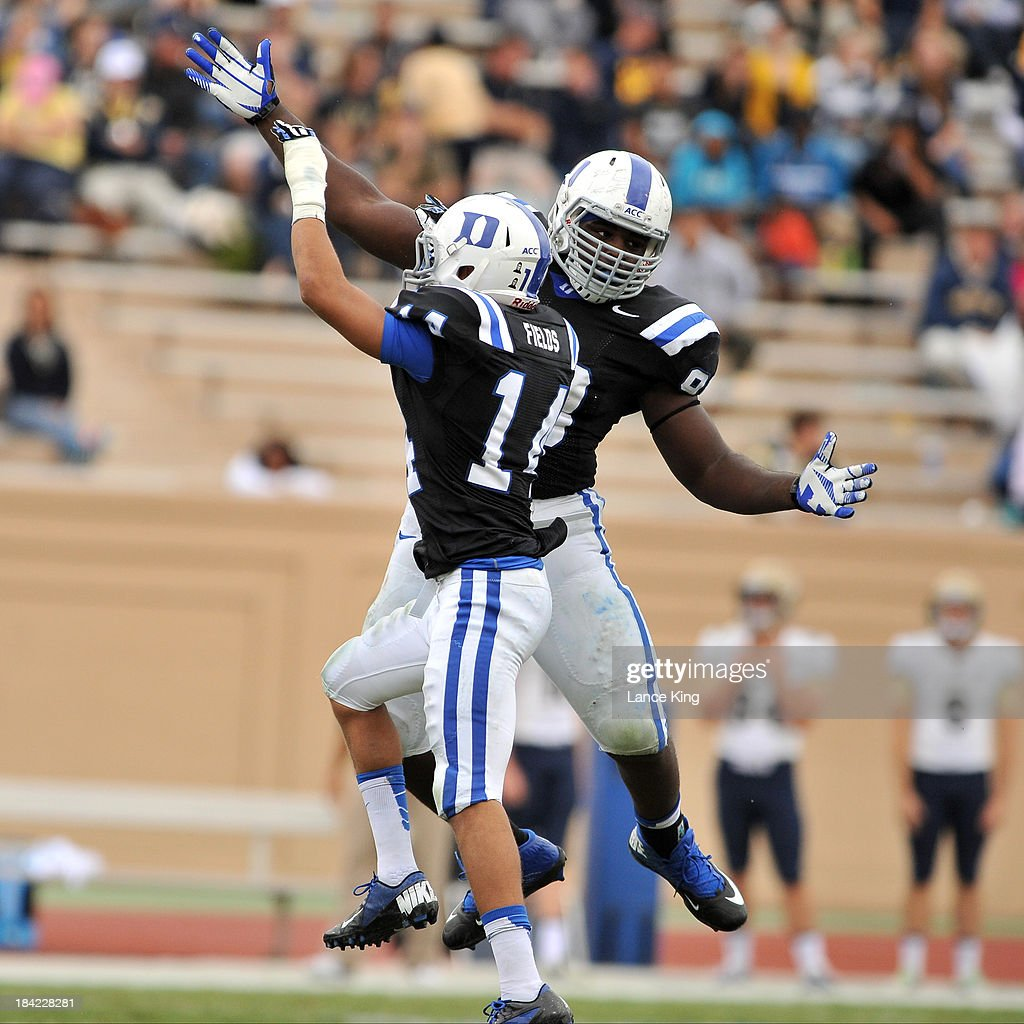 Carlos Wray #98 and Bryon Fields #14 of the Duke Blue Devils celebrate following a fumble recovery against the Navy Midshipmen at Wallace Wade Stadium on October 12, 2013 in Durham, North Carolina. Duke defeated Navy 35-7.