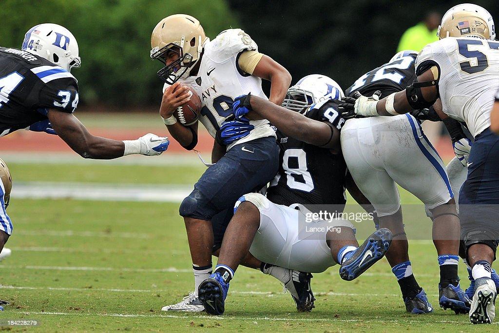 Carlos Wray #98 of the Duke Blue Devils tackles Keenan Reynolds #19 of the Navy Midshipmen at Wallace Wade Stadium on October 12, 2013 in Durham, North Carolina. Duke defeated Navy 35-7.