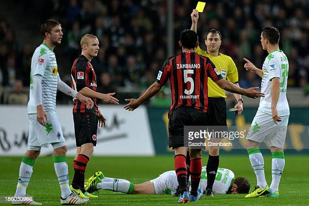 Carlos Zambrano of Frankfurt is booked yellow card by referee Felix Zwayer during the Bundesliga match between Borussia Moenchengladbach and...