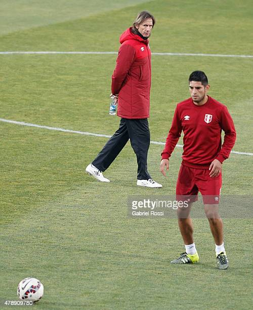 Carlos Zambrano of Peru watches the ball while Ricardo Gareca, coach of Peru, observes during a field scouting prior to the semi final match against...