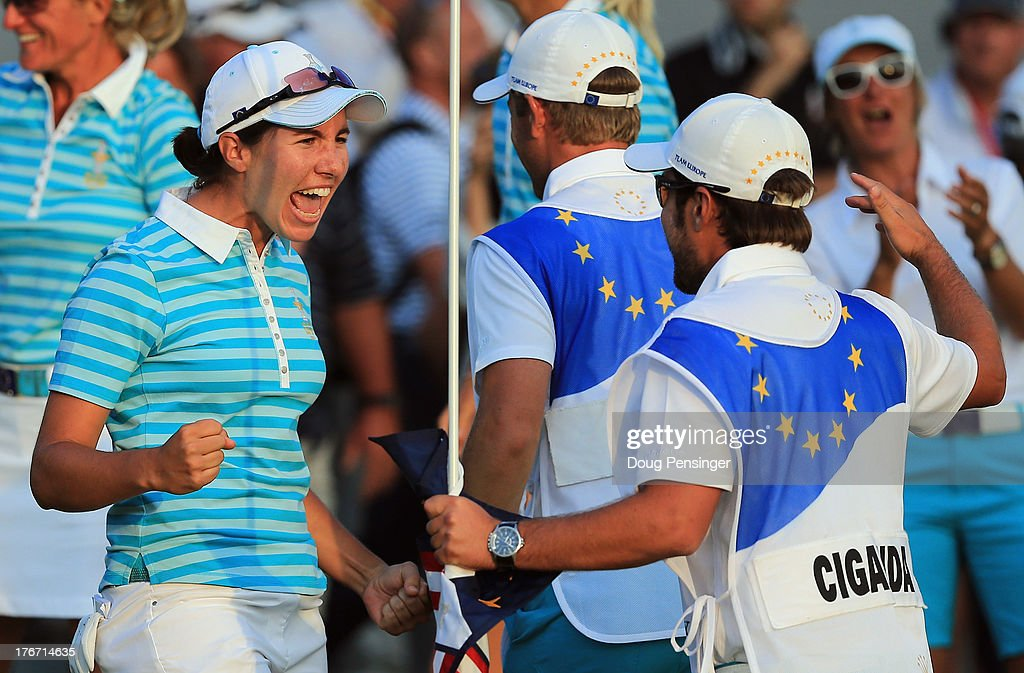 Carlota Ciganda of Spain and the European Team celebrates with her caddie Javier Urquizu after Ciganda made a birdie putt on the 18th hole to win the match with her teammate Azahara Munoz of Spain over Gerina Piller and Angela Stanford of the United States Team during the afternoon four-ball matches at the 2013 Solheim Cup on August 17, 2013 at the Colorado Golf Club in Parker, Colorado.