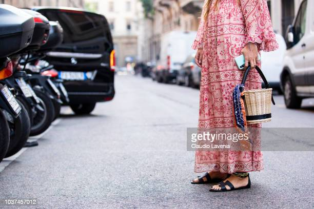 Carlotta Oddi, wearing red and white dress and Hermes black sandals, is seen before the Blumarine show during Milan Fashion Week Spring/Summer 2019...
