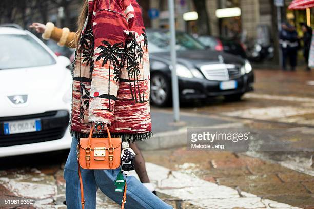 Carlotta Oddi wears a Saint Laurent red tropical themedcoat with a hood and a small orange Miu Miu purse at the Jil Sander show during the Milan...