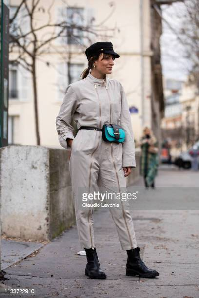 Carlotta Rubaltelli wearing a beige jumpsuit black boots black hat and teal and black Prada fanny pack is seen outside Sacai on Day 8 Paris Fashion...