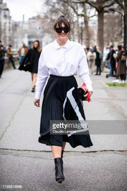 Carlotta Rubaltelli wearing a white Valentino shirt black Valentino midi skirt black boots and red Valentino bag is seen outside Valentino on Day 7...