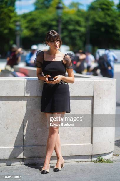 Carlotta Rubaltelli wears a black dress with lace on the shoulders Chanel slingback shoes outside Chanel during Paris Fashion Week Haute Couture...