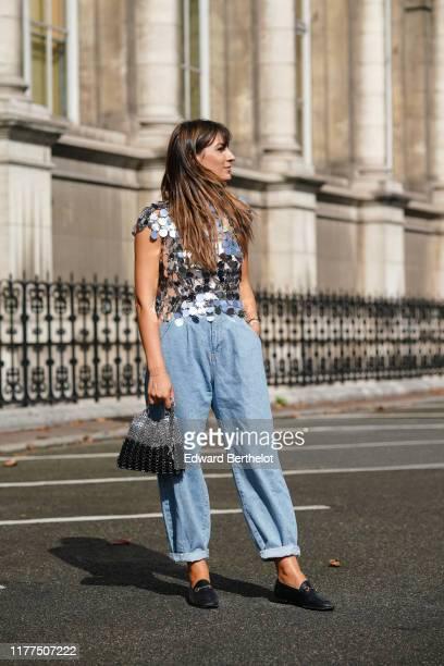 Carlotta Rubaltelli wears a glittering silver sequined top blue denim widelegs rolledup hem pants a black and metal mesh bag black moccasins outside...