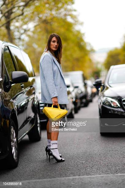 Carlotta Rubaltelli wears a yellow balenciaga triangle bag a gray jacket a black dress with mesh Vans socks black heels shoes outside Valentino...