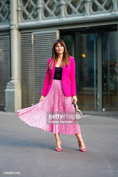 Carlotta Rubaltelli wears earrings, a necklace, a black top, a neon-pink jacket, a Miu Miu pink pleated skirt, a white Valentino bag, rhinestone...