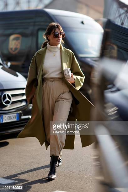 Carlotta Rubaltelli wears sunglasses, a white turtleneck pullover, a necklace, a green / khaki long coat, pale brown beige pants, pointy leather...
