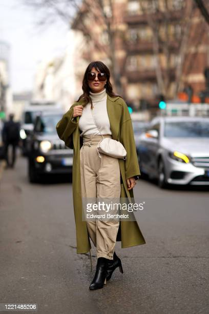 Carlotta Rubaltelli wears sunglasses, a white turtleneck pullover, a khaki long coat, a Bottega Veneta leather Pouch bag, beige pants, black leather...