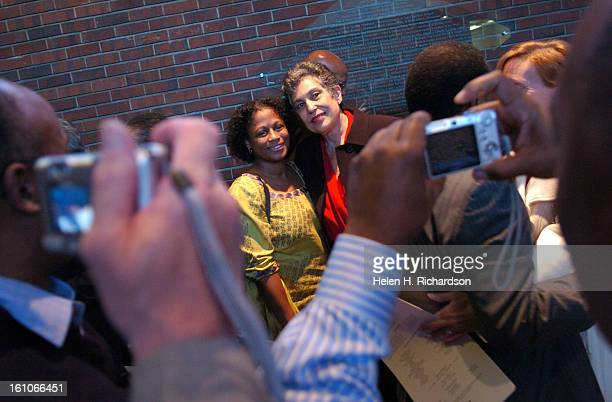Carlotta Walls LaNier <cq> right poses for photographs with eager fans after the interfaith service at Congregation Emanuel <cq> The nine members of...
