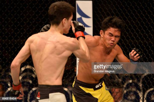 Carls John De Tomas of the Philippines punches Naoki Inoue of Japan in their flyweight bout during the UFC Fight Night event at the Singapore Indoor...