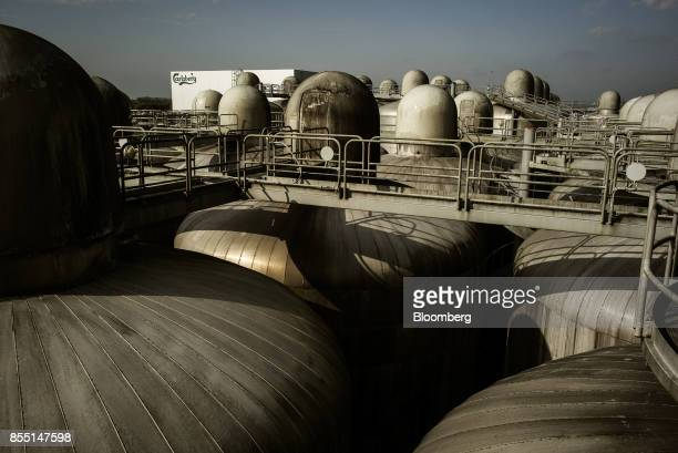 A Carlsberg logo sits on a building beyond beer tanks at the Carlsberg A/S brewery in Fredericia Denmark on Wednesday Sept 27 2017 The company aims...