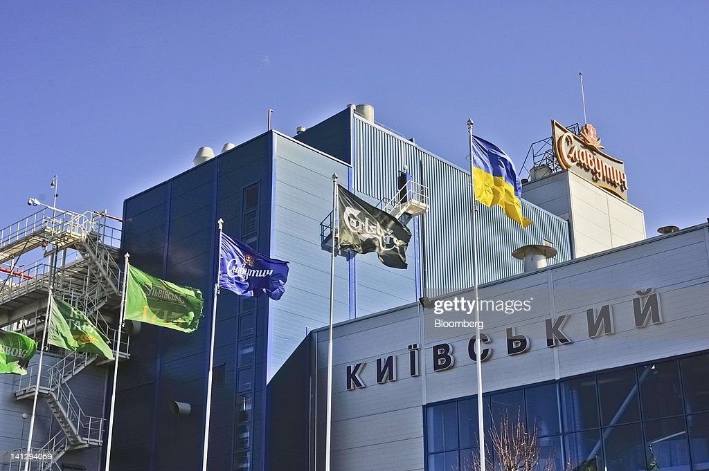 A Carlsberg-branded flag flies besides a Ukrainian national flag, right, outside the Carlsberg A/S production plant in Kiev, Ukraine, on Wednesday, March 14, 2012. Sales in the Ukraine were 'significantly higher,' helped by better economic conditions and the recent introduction of premium beers, while the U.K. saw 'continuing strong growth,' the brewer said. Photographer: Vincent Mundy/Bloomberg via Getty Images