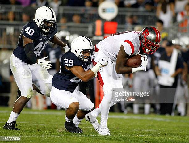 Carlton Agudosi of the Rutgers Scarlet Knights makes a catch and is tackled by John Reid of the Penn State Nittany Lions in the second half during...