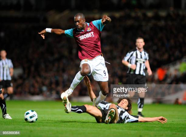 Carlton Cole of West Ham United hurdles a challenge from Fabricio Coloccini of Tottenham Hotspur during the Barclays Premier League match between...