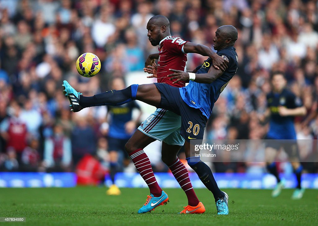 Carlton Cole of West Ham United is challenged by Eliaquim Mangala of Manchester City during the Barclays Premier League match between West Ham United and Manchester City at Boleyn Ground on October 25, 2014 in London, England.