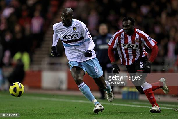 Carlton Cole of West Ham United is pursued by John Mensah of Sunderland during the Barclays Premier League match between Sunderland and West Ham...