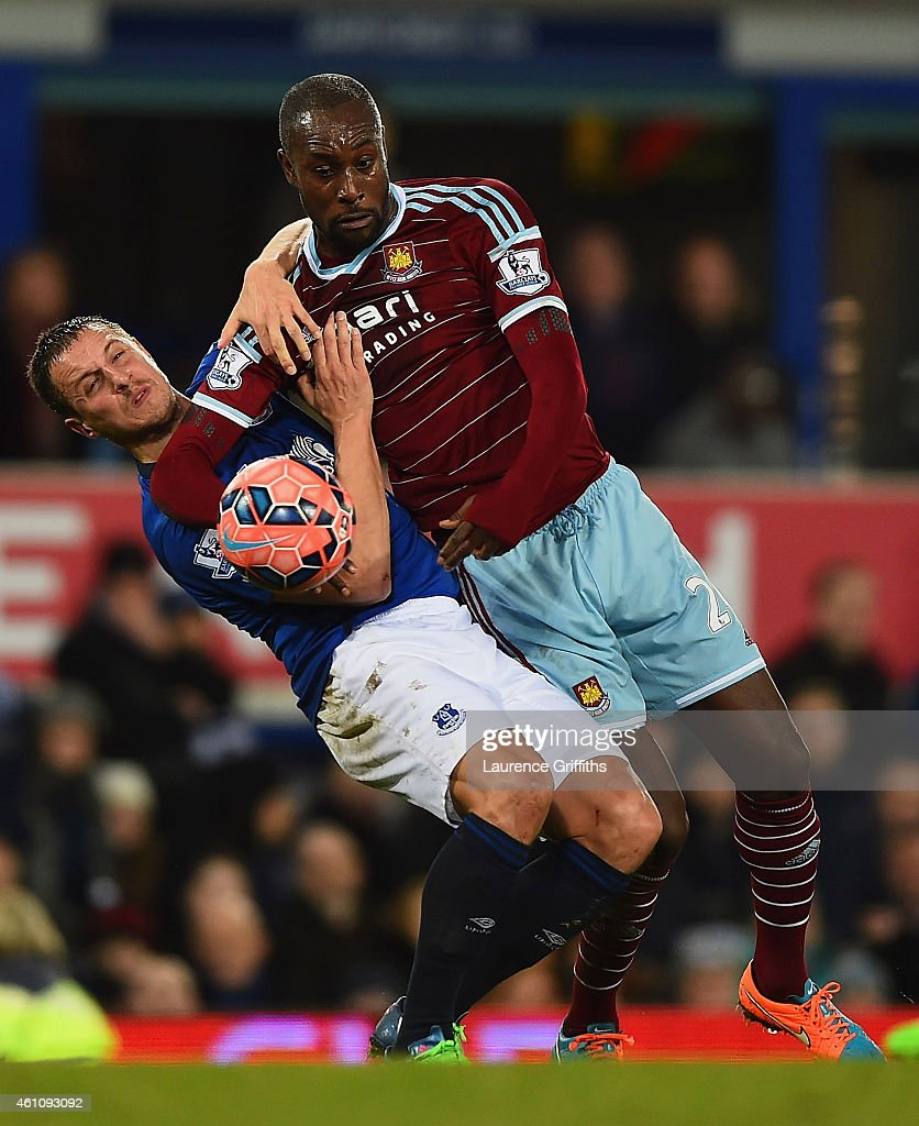 Carlton Cole of West Ham United tangles with Phil Jagielka of Everton during the FA Cup Third Round match between Everton and West Ham United at Goodison Park on January 6, 2015 in Liverpool, England.