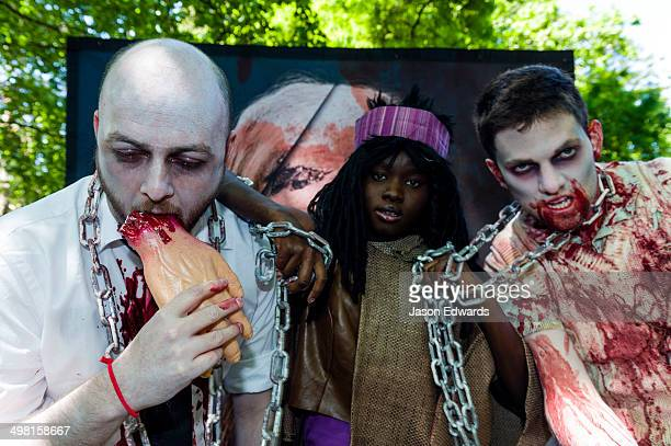 People dressed as zombies held by chains by a character from the Walking Dead eating a hand.