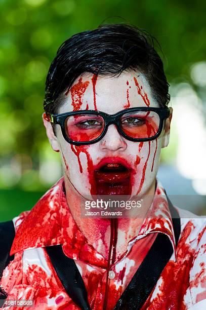 A drooling, blood-soaked zombie wearing glasses at a festival.
