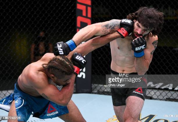 Carlton Minus and Matthew Semelsberger trade punches in their welterweight fight during the UFC Fight Night event at UFC APEX on August 22, 2020 in...
