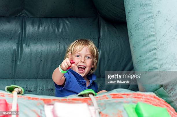 A boy laughing as he plays on an inflatable castle at a school fete.