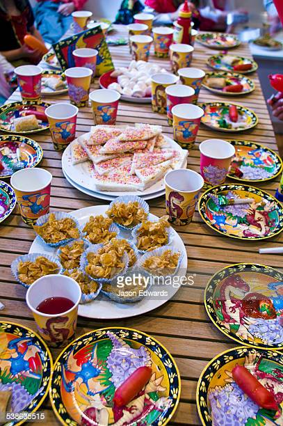 Party food and drinks fill a table at a childrens birthday party.