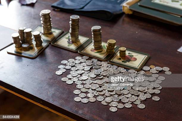 Coins from a childs money-box being sorted into their currency denominations for counting at the bank.