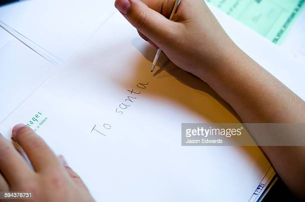 A boy writing a letter to Santa Claus letting him know what toys he would like.