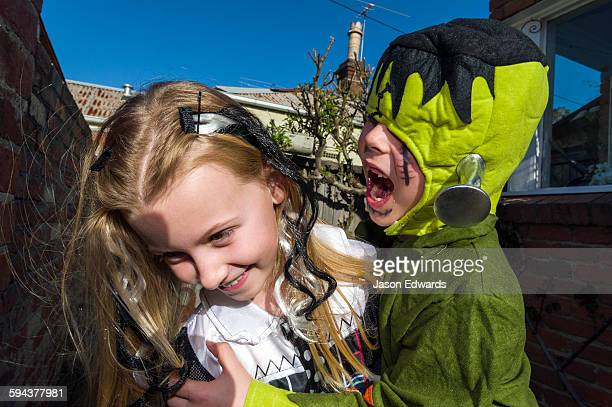 A boy dressed as Frankenstein tries to bite a girl at a monster party.