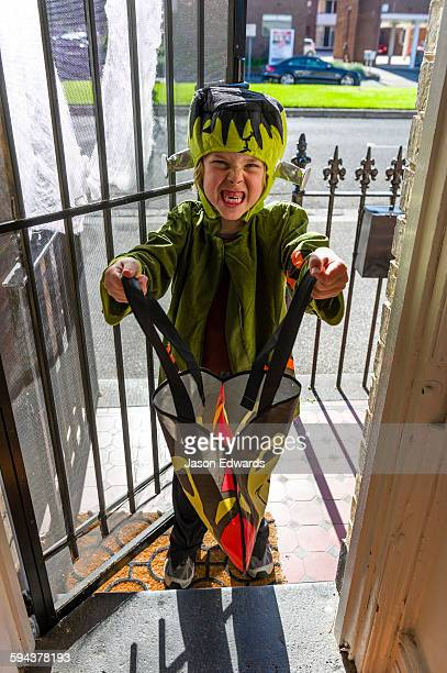A boy dressed as Frankenstein demands candy during trick or treat on Halloween.