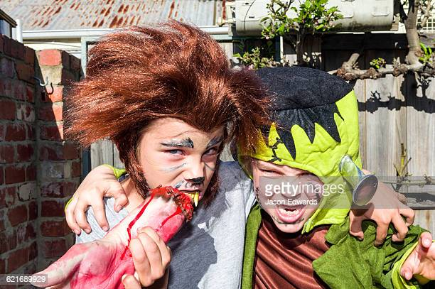 Two friends, a werewolf and Frankenstein, hug each other at a monster party.