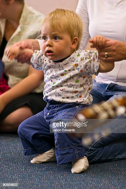 A baby dancing to songs and a guitar in a children's music class.