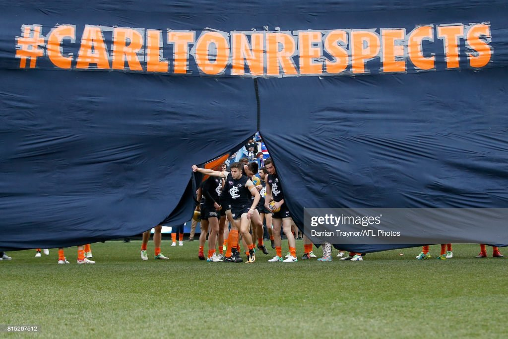 Carlton players run through the banner before the round 17 AFL match between the Carlton Blues and the Western Bulldogs at Melbourne Cricket Ground on July 16, 2017 in Melbourne, Australia.