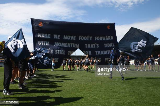 Carlton players run through their team banner during the AFLW Preliminary Final match between the Carlton Blues and the Fremantle Dockers at Ikon...