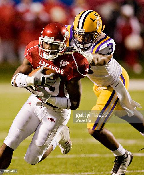 Carlton Salters of the Arkansas Razorbacks is grabbed from behind by Chad Jones of the LSU Tigers at War Memorial Stadium on November 28, 2008 in...